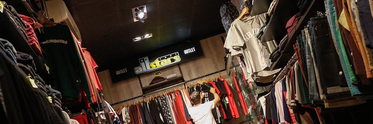 chico busca ropa en el estante del fondo de la tienda de Barcelona
